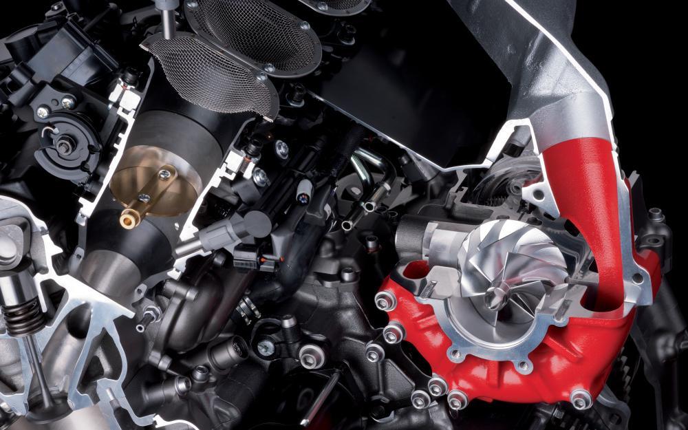 """Spaccato del 4 cilindri 999 cc della Kawasaki Ninja H2R. Sovralimentato tramite un compressore centrifugo azionato a catena, eroga 300 CV nella versione """"solo pista"""". La versione stradale dovrebbe avere potenza di """"almeno"""" 200 CV. Le punterie """"normalmente"""" a bicchierini e molle indicano che il regime massimo di rotazione non è elevatissimo. Notare il doppio iniettore."""