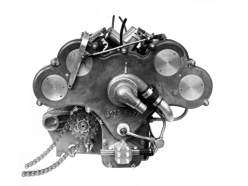 """Moto Guzzi 8 cilindri GP 500 (1955-57): immagine ufficiale arrivata da Guzzi. Il grosso """"buco"""" all'estremità del carter dietro il pignone di trasmissione finale supporta il forcellone in tubi tondi. Sopra la scritta """"MOTO GUZZI"""" sul carter della distribuzione, la pompa dell'acqua di raffreddamento e sotto, quella dell'olio."""