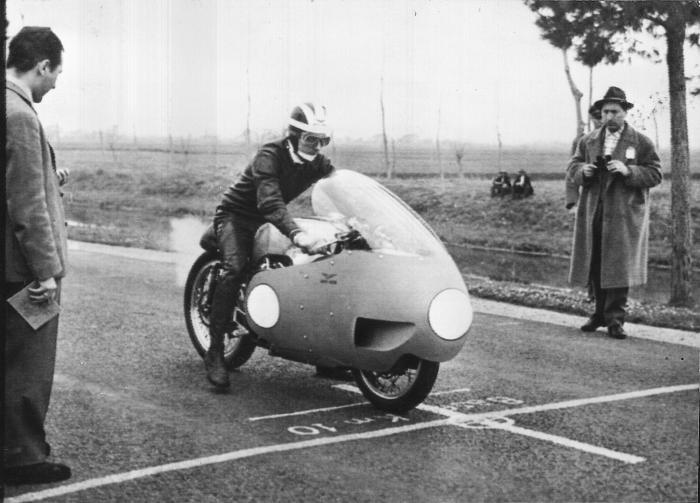 """Moto Guzzi 8 cilindri GP 500 (1955-57): 26 febbraio 1957, Bill Lomas a Terracina (RM), sulla famosa """"fettuccia"""", tenta di battere il record di velocità sui 10 km da fermo. Riuscirà nell'impresa, alla media di 243,572 km/h e uscendo dalla base cronometrata a 282 km/h."""