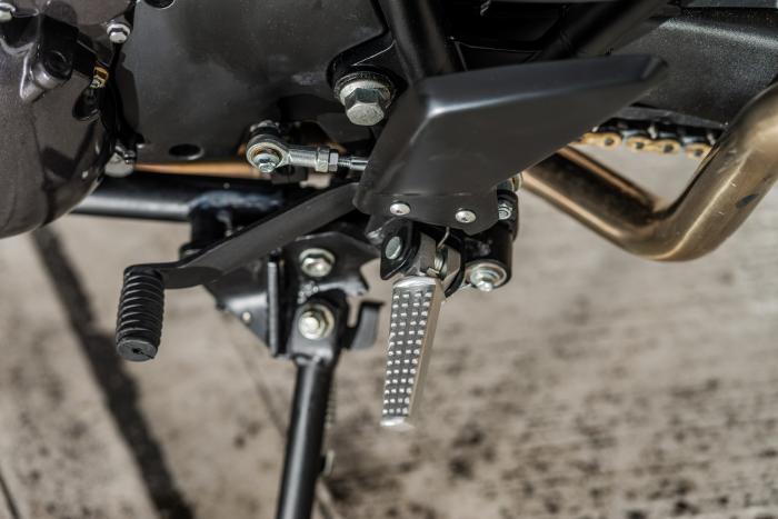 Le pedane sono in alluminio zigrinato, abbastanza sportive. Di semplice lamiera verniciata invece la leva del cambio, così come il pedale del freno, sull'altro lato